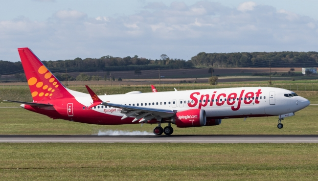 A SpiceJet Boeing 737 Max aircraft touching down landing on a runway
