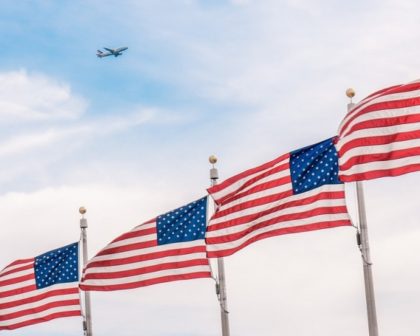 Aircraft flying over a row of American flags