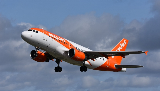 An EasyJet Airbus A320 jet climbing in flight with landing gear and flaps down. Cumulus clouds in the background