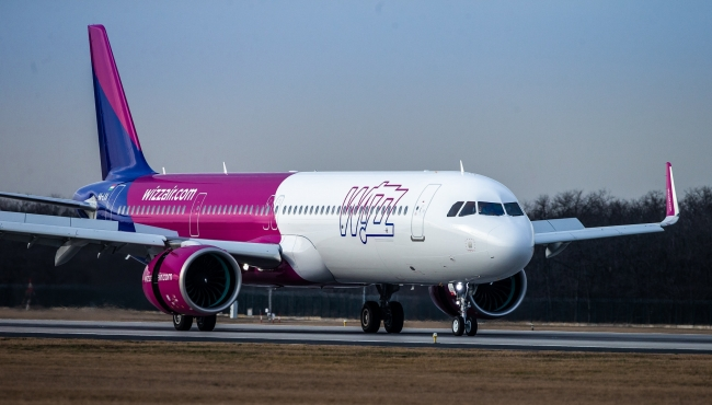 A Wizz Air A321 NEO aircraft on an airport runway, with thrust reversers and spoilers open, and landing gear down.